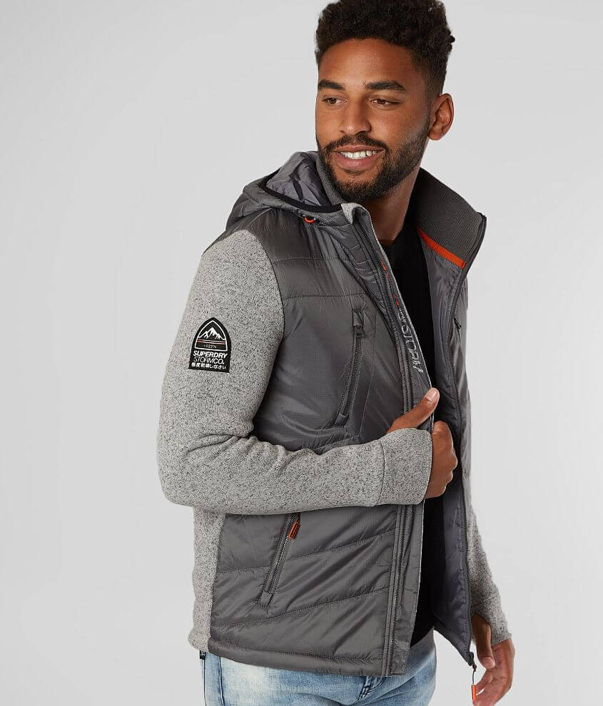 Quilted zip front lined jacket Heathered knit fleece lined sleeves Ribbed knit collar Front zipper pockets Embroidered patch sleeve hit Cinch tie hem Thumbhole detail Model Info: Height: 6\\\'0\\\